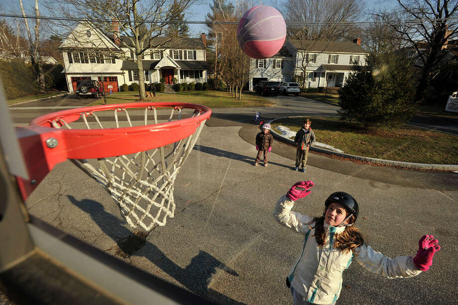 Isabelle Ritchie, right, shoots a basketball as her siblings, Lily and James, watch near their home in Greenwich, Conn., on Sunday, Jan. 19, 2014. Photo: Jason Rearick / Stamford Advocate