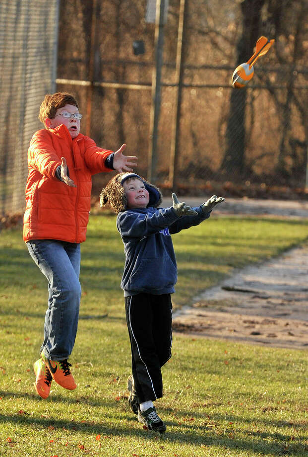 Bradley Negrin, left, and neighbor friend Jackson Steele compete to catch a football behind Old Greenwich School in Greenwich, Conn., on Sunday, Jan. 19, 2014. Photo: Jason Rearick / Stamford Advocate