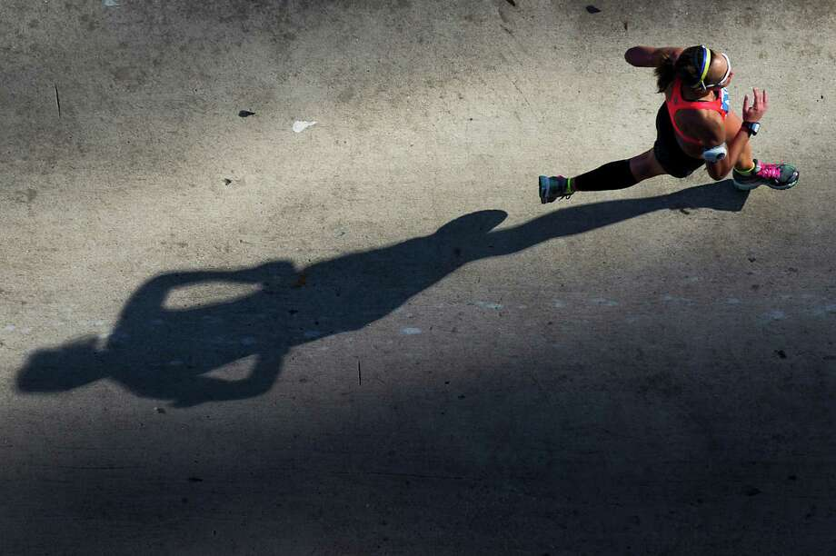 A runner casts a long shadow as she heads for the final mile of the Chevron Houston Marathon. Photo: Smiley N. Pool, Houston Chronicle / © 2014  Houston Chronicle