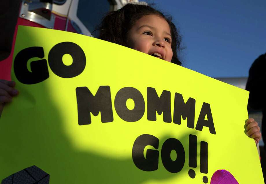 Jayden Flores, 4, holds up her sign as she waits for her mother Myrna to run down Washington Ave. Photo: J. Patric Schneider, For The Chronicle / © 2014 Houston Chronicle