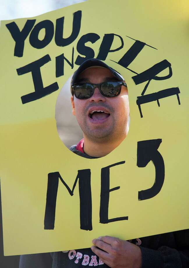 Johan Espitia holds up a sign as runners compete during the Chevron Houston Marathon. Photo: J. Patric Schneider, For The Chronicle / © 2014 Houston Chronicle