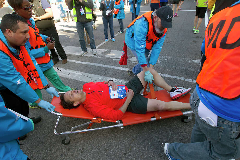 Volunteers wheel a runner out on a stretcher at the finish line of the Chevron Houston Marathon. Photo: Cody Duty, Houston Chronicle / © 2014 Houston Chronicle