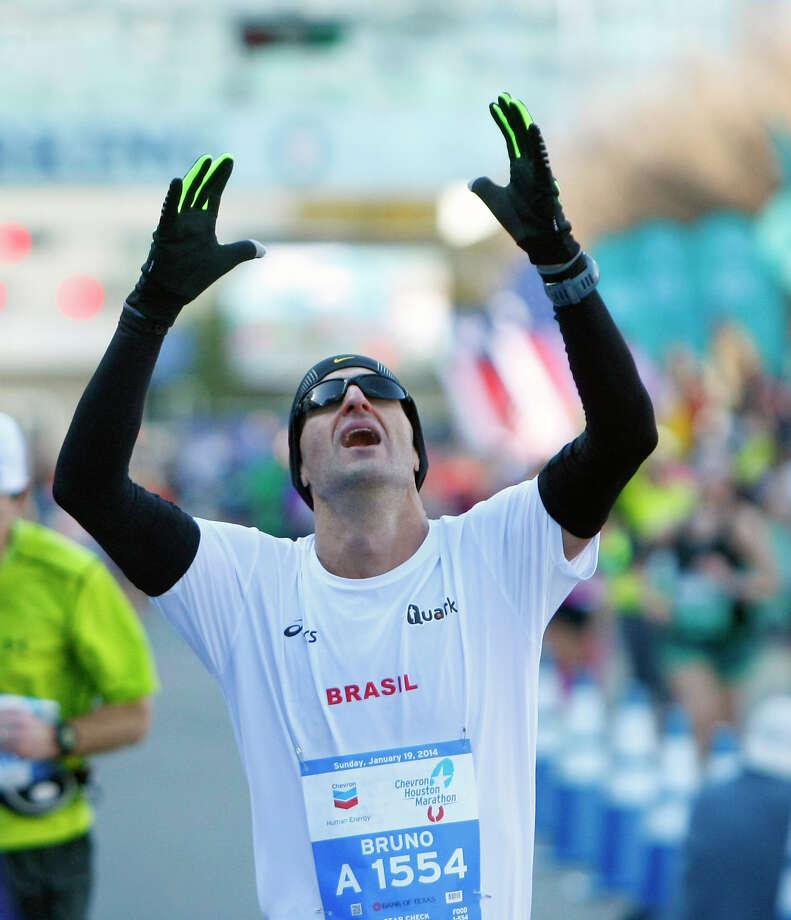 A runner crosses the finish line of the Chevron Houston Marathon. Photo: Cody Duty, Houston Chronicle / © 2014 Houston Chronicle