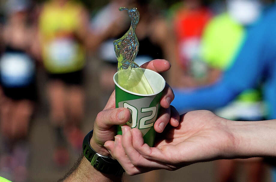A runner is handed a cup of Gatorade as he runs by on Memorial Dr. during the Chevron Houston Marathon. Photo: J. Patric Schneider, For The Chronicle / © 2014 Houston Chronicle