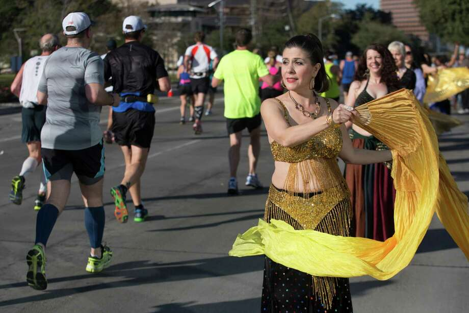 Veralisa Waterwall with the Sirrom Dance Studio performs a belly dance as runners make their way on Post Oak Blvd. The group has been dancing at the marathon for over 30 years. Photo: J. Patric Schneider, For The Chronicle / © 2014 Houston Chronicle