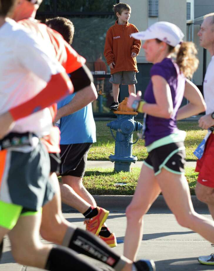 Dash Levy, 8, gets a little higher view of the runners as they pass on Post Oak Ave. Photo: J. Patric Schneider, For The Chronicle / © 2014 Houston Chronicle