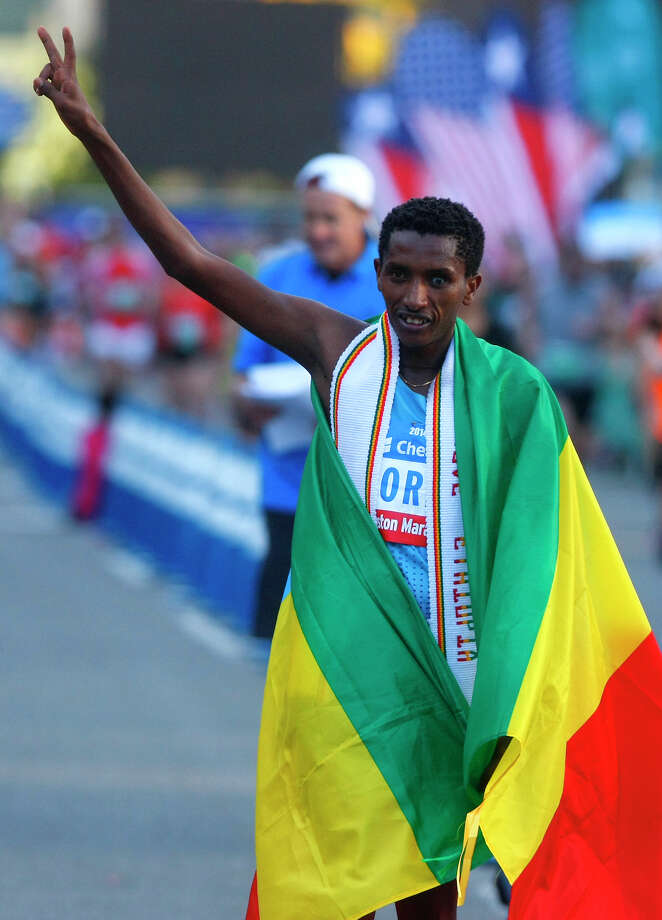 Bazu Worku, of Ethiopia, celebrates at the finish line of the Chevron Houston Marathon after winning with a time of 2:07:32. Photo: Cody Duty, Houston Chronicle / © 2014 Houston Chronicle