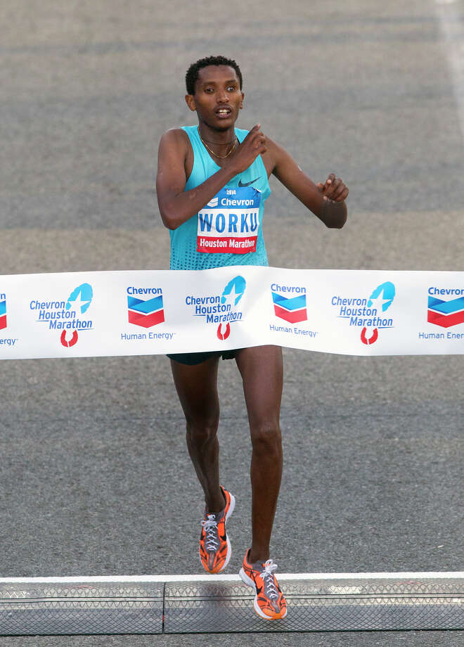 Bazu Worku, of Ethiopia, crosses the finish line of the Chevron Houston Marathon to win with a time of 2:07:32. Photo: Cody Duty, Houston Chronicle / © 2014 Houston Chronicle