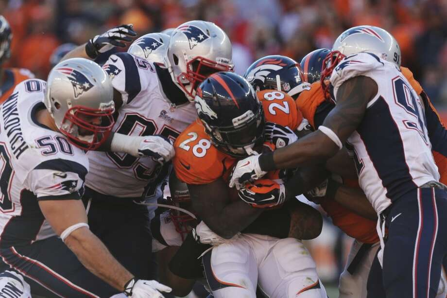 Broncos running back Montee Ball is tackled by a gang of Patriots defenders. Photo: Julie Jacobson, Associated Press