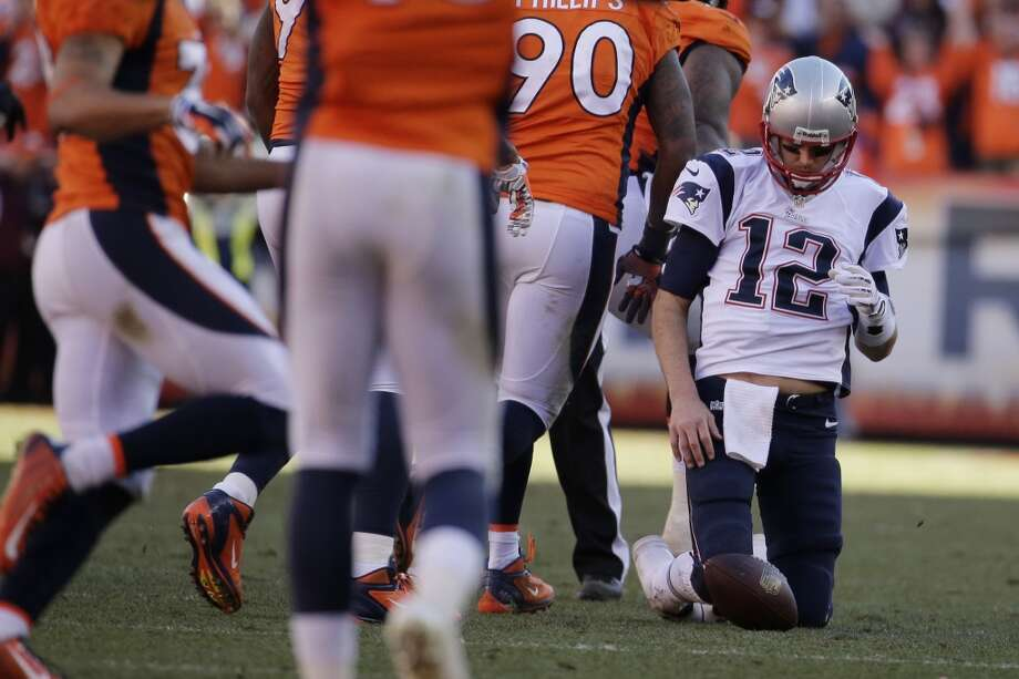 Patriots quarterback Tom Brady gets up after being sacked against the Broncos. Photo: Charlie Riedel, Associated Press