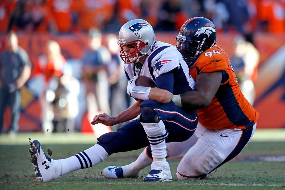 Patriots quarterback Tom Brady is brought down for a sack against the Broncos. Photo: Kevin C. Cox, Getty Images