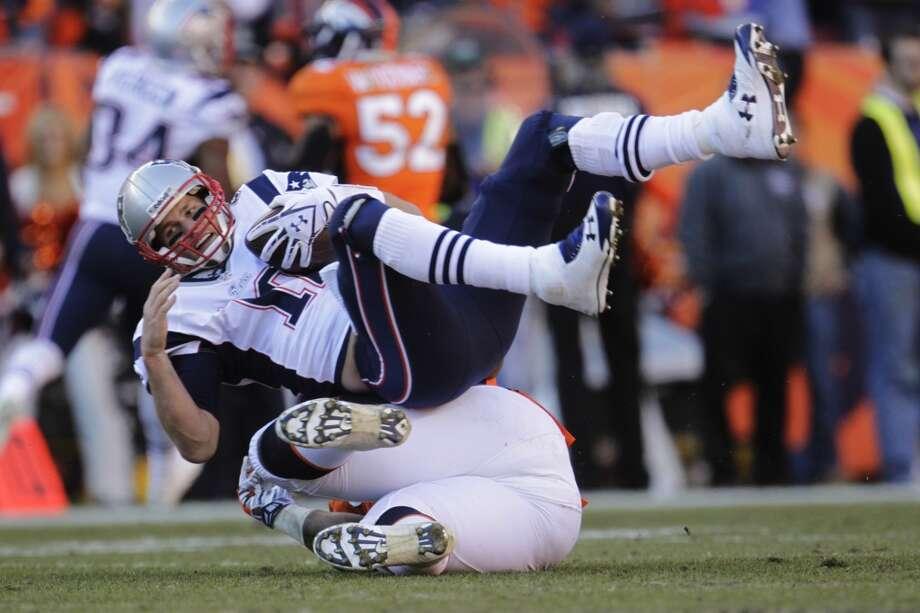 Patriots quarterback Tom Brady is brought down for a sack against the Broncos. Photo: Joe Mahoney, Associated Press