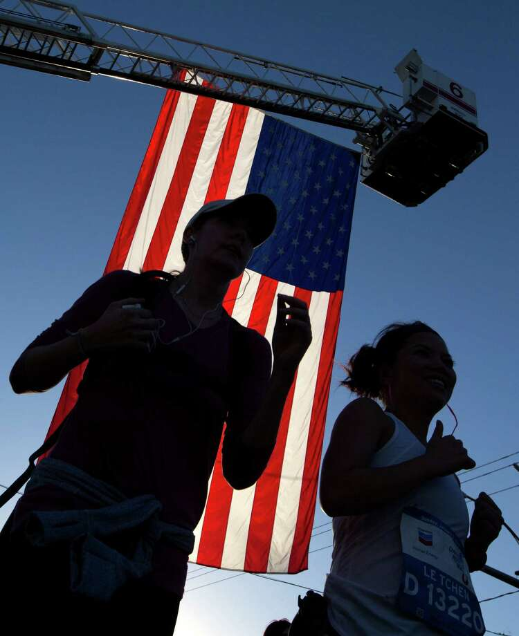 Runners pass under a large American flag at Houston Fire Station #6 on Washington Ave. Photo: J. Patric Schneider, For The Chronicle / © 2014 Houston Chronicle