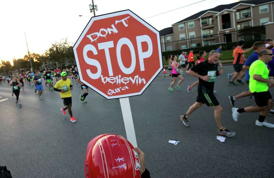 A spectator holds a sign as runners run down Washington Ave. Photo: J. Patric Schneider, For The Chronicle / © 2014 Houston Chronicle