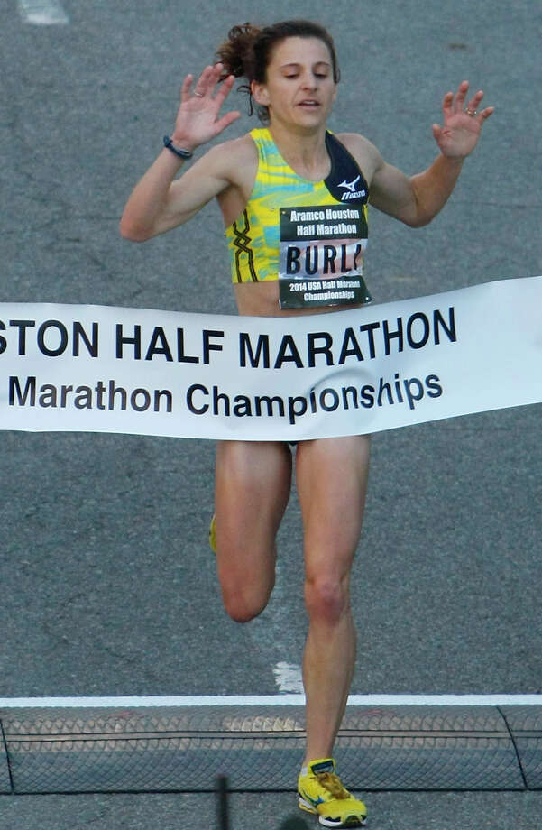 Serena Burla is the first woman to cross the finish line of the Aramco Houston Half Marathon with a 1:10:48 finish. Photo: Cody Duty, Houston Chronicle / © 2014 Houston Chronicle