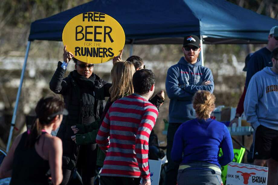 A spectators holds sign offering beer to runners in the Aramco Houston Half Marathon. Photo: Smiley N. Pool, Houston Chronicle / © 2014  Houston Chronicle