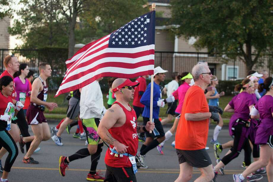A runner carries an American Flag as he runs down Washington Ave. Photo: J. Patric Schneider, For The Chronicle / © 2014 Houston Chronicle