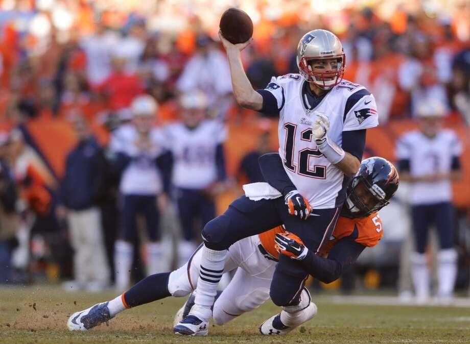 Patriots quarterback Tom Brady is pressured by a Broncos defender. Photo: Jack Dempsey, Associated Press