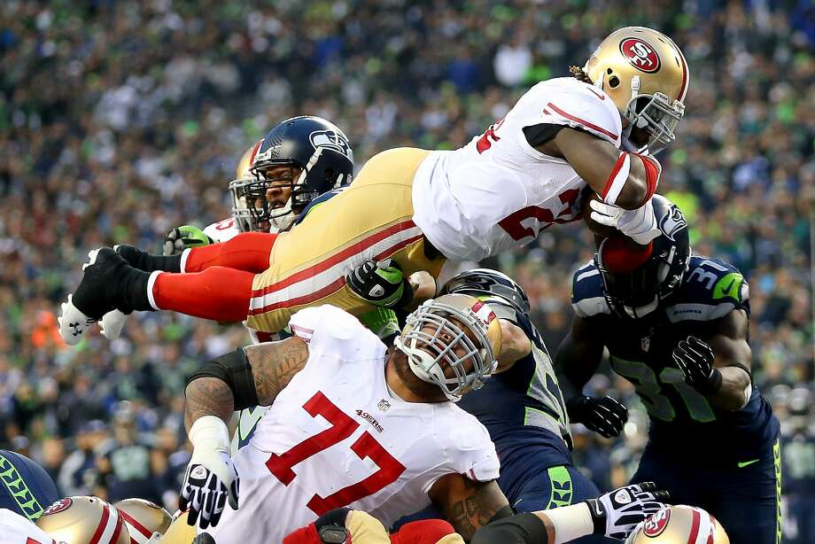 SEATTLE, WA - JANUARY 19:  Running back Anthony Dixon #24 of the San Francisco 49ers dives into the endzone against defensive end Red Bryant #79 of the Seattle Seahawks to score a one-yard touchdown in the first half against the Seattle Seahawks during the 2014 NFC Championship at CenturyLink Field on January 19, 2014 in Seattle, Washington.  (Photo by Ronald Martinez/Getty Images) Photo: Ronald Martinez, Getty Images
