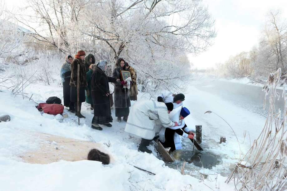 Two believers support a Russian Orthodox priest blessing water in a river on the eve of Russian Orthodox Epiphany in the village of Fedorovskoye, some 100 km (63 miles) southeast of Moscow, Saturday, Jan. 18, 2014. Water that is blessed by a cleric on Epiphany is considered holy and pure and believed to have special powers of protection and healing. Thousands of Russian Orthodox Church followers will plunge into icy rivers and ponds across the country to mark Epiphany, cleansing themselves with water deemed holy for the day. Photo: Vladimir Khodakov, AP / AP