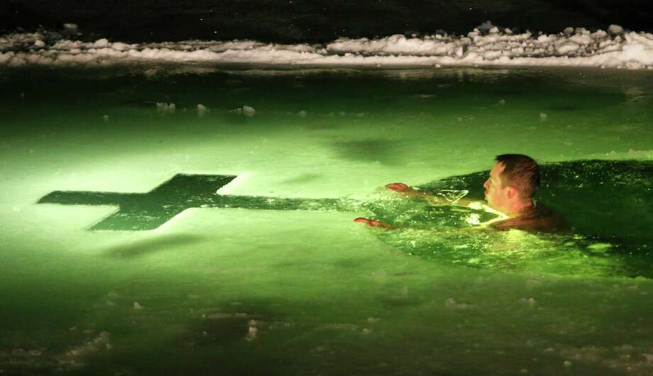 A man swims in the ice cold water of a lake on the eve of Russian Orthodox Epiphany in Minsk, Belarus, late Saturday, Jan. 18, 2014. Orthodox Church believers celebrate Epiphany on Jan. 19. Photo: Sergei Grits, AP / AP