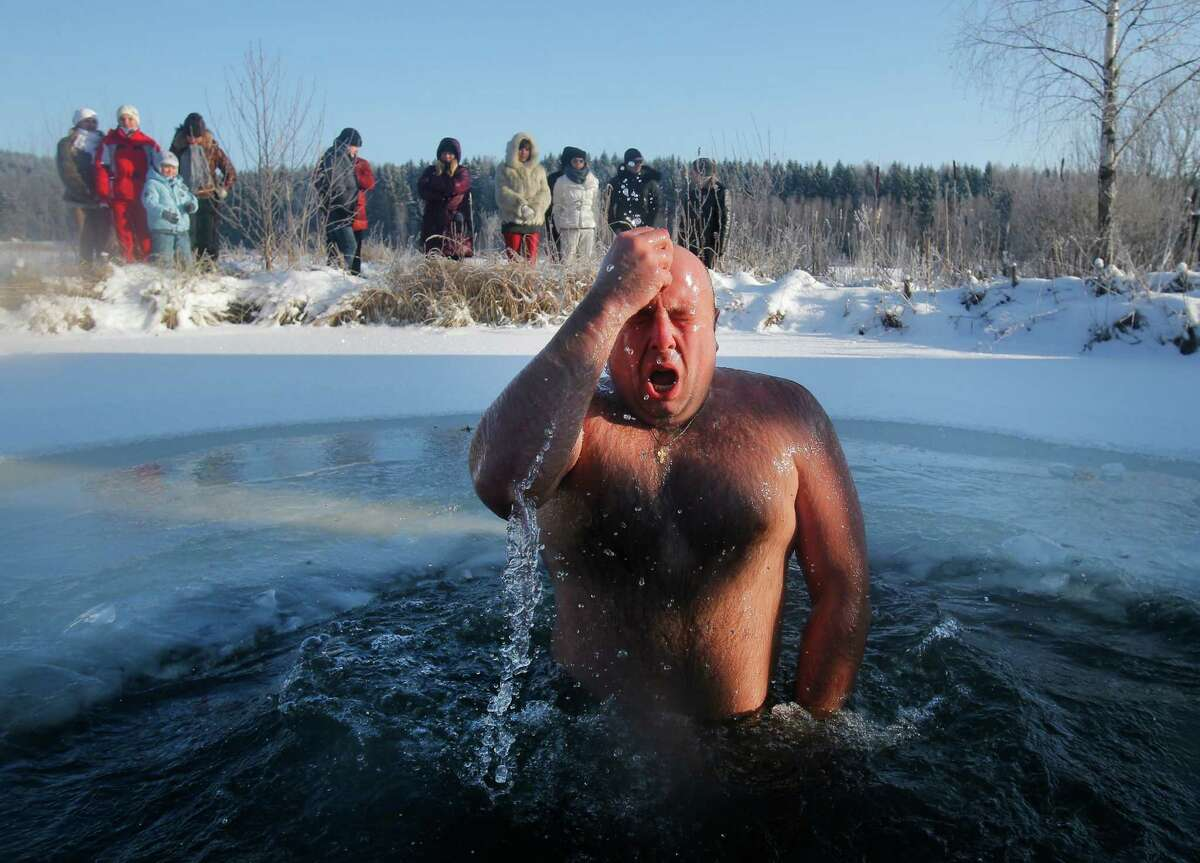 A man crosses himself while bathing in the ice cold water after plunging into it during Orthodox Epiphany celebrations at a lake in the village of Zadomlya, Belarus, Sunday, Jan. 19, 2014. Thousands of Belarusian Orthodox Church followers plunged into icy rivers and ponds across the country to mark Epiphany, cleansing themselves with water deemed holy for the day.