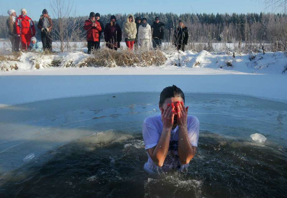 A woman reacts in the ice cold water after plunging into it during Orthodox Epiphany celebrations at a lake in the village of Zadomlya, Belarus, Sunday, Jan. 19, 2014. Thousands of Belarusian Orthodox Church followers plunged into icy rivers and ponds across the country to mark Epiphany, cleansing themselves with water deemed holy for the day. Photo: Sergei Grits, AP / AP