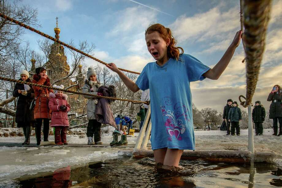 A girl bathes in an icy cold water during a celebration of Epiphany not far away from Saint-Petersburg on January 19, 2014 in Petergof, Russia. According to traditions of the Russian Orthodox Church, Russians bathe in lakes or rivers just after the midnight of Epiphany. Photo: Kommersant Photo, Getty Images / 2014 Kommersant Photo