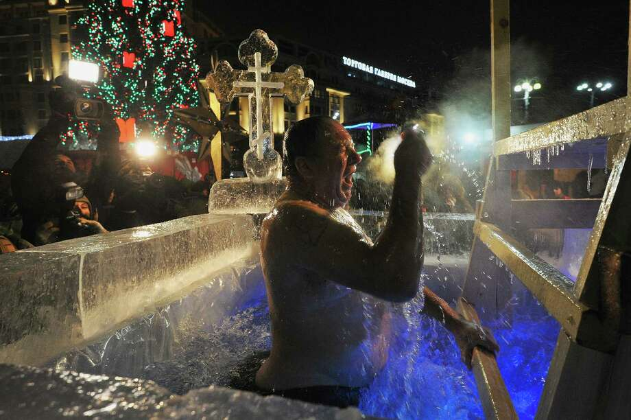MOSCOW, RUSSIA - JANUARY 19: A man bathes in an icy cold water as air temperature is - 22 C during a celebration of Epiphany in the center of Moscow nearby Red Square on January 19, 2014 in  Moscow, Russia. According to traditions of the Russian Orthodox Church, Russians bathe in lakes or rivers just after the midnight of Epiphany. Photo: Kommersant Photo, Getty Images / 2014 Kommersant Photo