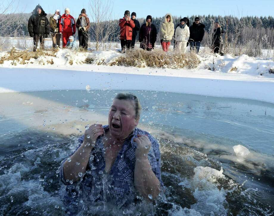 Belarussians dip themselves into the icy water of a lake near the village of Zadomlia, some 40 km east of Minsk, January 19, 2014. AFP PHOTO / VIKTOR DRACHEV Photo: VIKTOR DRACHEV, Getty Images / 2014 AFP