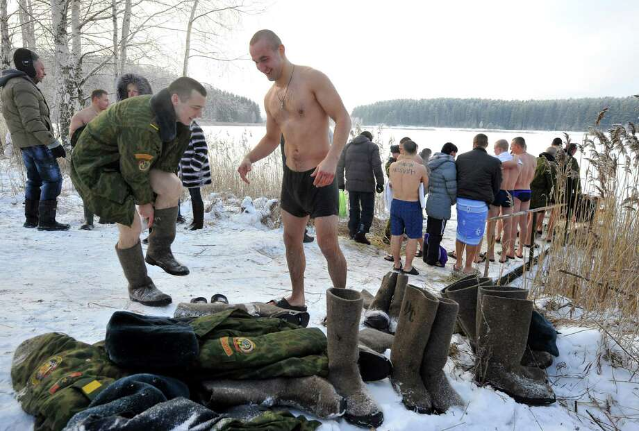 Servicemen of the Belarussian Interior Ministry's special unit wait in a queue to dip themselves into the icy water of a lake near the village of Zadomlia, some 40 km east of Minsk, January 19, 2014. AFP PHOTO / VIKTOR DRACHEV Photo: VIKTOR DRACHEV, Getty Images / 2014 AFP