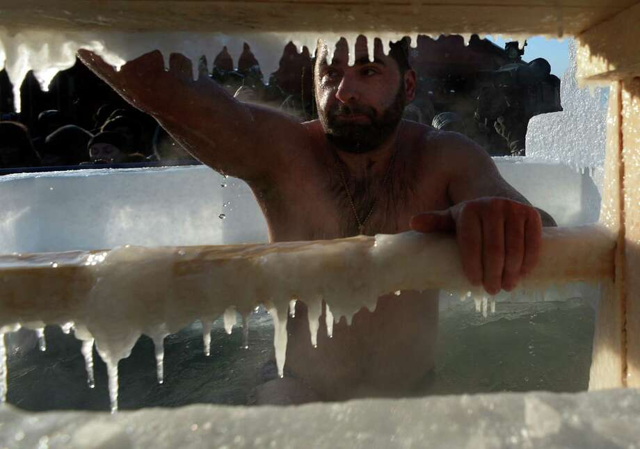 A Russian Orthodox man bathes in ice cold water near the Red Square in Moscow during a ceremony marking Epiphany on January 19, 2014. AFP PHOTO / VASILY MAXIMOV Photo: AFP, Getty Images / 2014 AFP