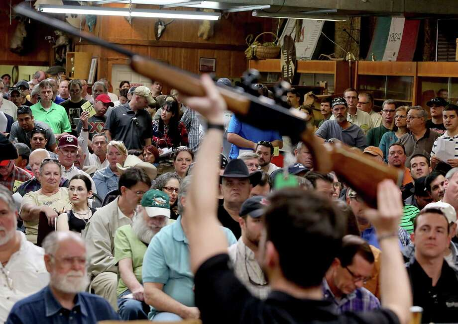 A bidder bids on a Browning 8500 shotgun at the auction January 19, 2014.  Over 90 guns, ammunition, gun accessories, a BBQ trailer, a police motorcycle, coins, animals skins and taxidermy of Dr. Michael G. Brown items were auctioned at the Webster's Auction Palace in Houston, Texas. Photo: Thomas B. Shea, The Houston Chronicle / © 2014 Thomas B. Shea