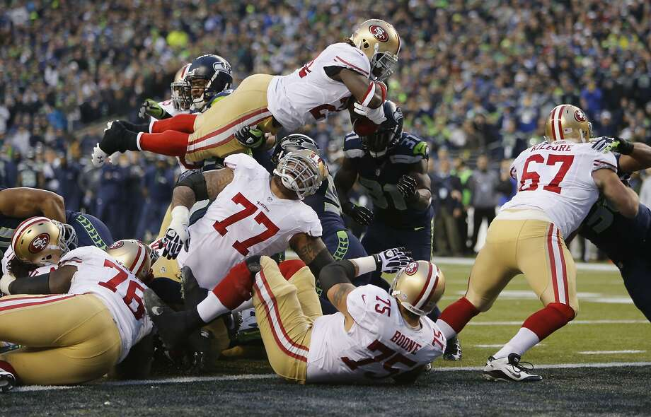 Anthony Dixon soars into the end zone for a second-quarter TD as 49ers lineman Mike Iupati (77) shows a pained reaction to a play on which he was injured. Photo: Michael Macor, The Chronicle