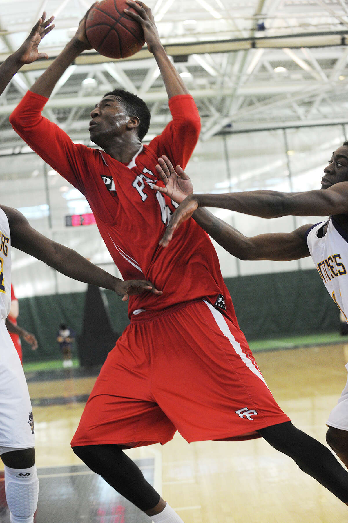 Fairfield Prep's Paschal Chukwu drives to the basket against two Career High School defenders during the Jesuits' boys basketball matchup at the Floyd Little Athletic Center in New Haven, Conn. on Sunday, January 19, 2014.