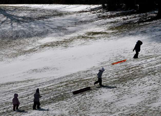 Children make their way back up a hill at Capital Hills at Albany golf course for another slide down on Sunday, Jan. 19, 2014 in Albany, NY.  (Paul Buckowski / Times Union) Photo: Paul Buckowski