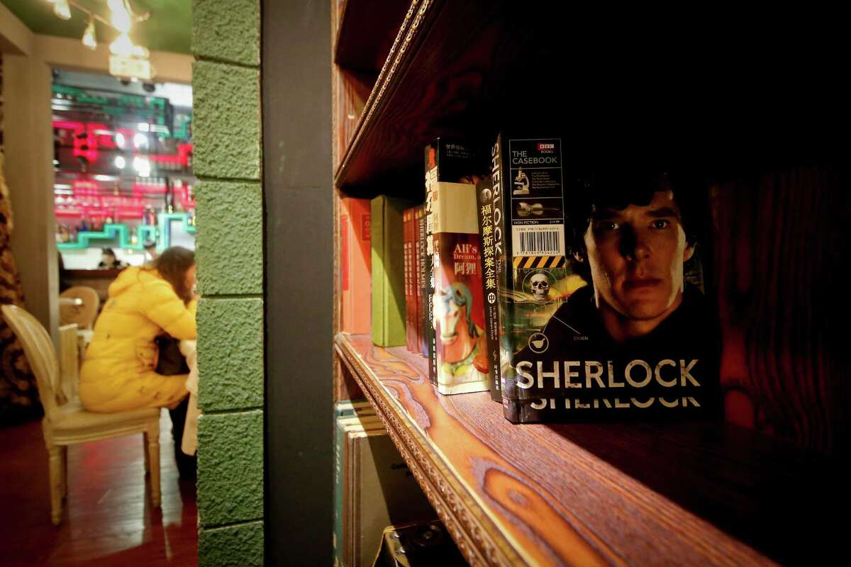 """In this photo taken on Friday, Jan. 17, 2014, a girl has a drink near books shelf displaying Sherlock Holmes books at a """"Sherlock""""-themed cafe in Shanghai, China. """"Sherlock?'?' has become a global phenomenon, but nowhere more than in China, where fans?' devotion is so intense that the BBC says this was the first country outside Britain where the new season was shown. (AP Photo) ORG XMIT: XBEJ102"""