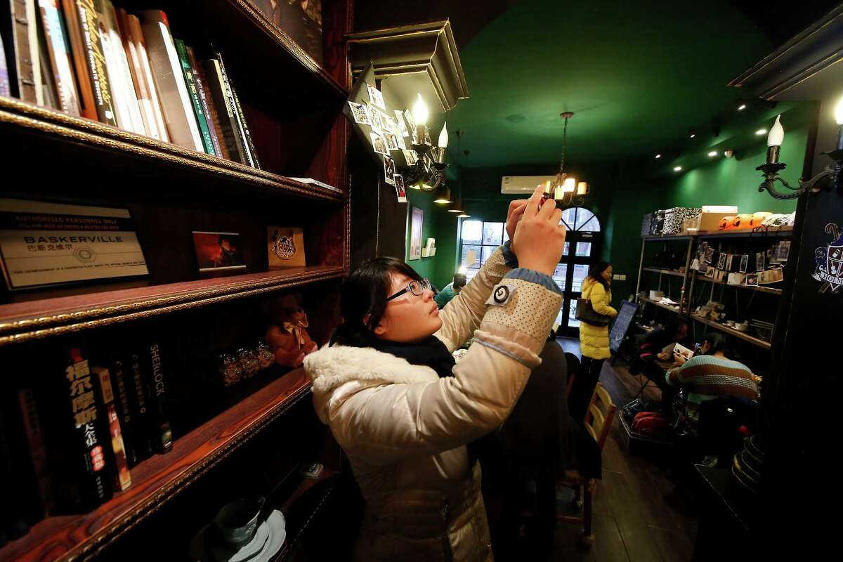 """In this photo taken on Friday, Jan. 17, 2014, a girl takes pictures at a """"Sherlock""""-themed cafe in Shanghai, China. """"Sherlock?'?' has become a global phenomenon, but nowhere more than in China, where fans?' devotion is so intense that the BBC says this was the first country outside Britain where the new season was shown. (AP Photo) ORG XMIT: XBEJ101"""
