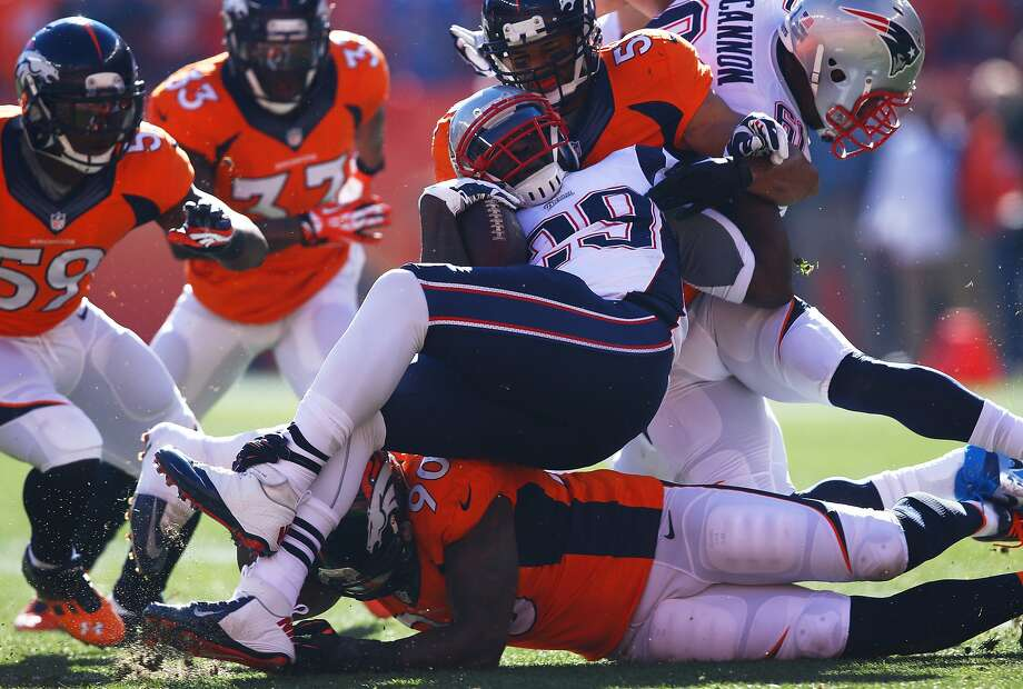 New England's LeGarrette Blount, tackled by Paris Lenon (top) and Shaun Phillips, rushed for only 6 yards on five carries. Photo: Doug Pensinger, Getty Images