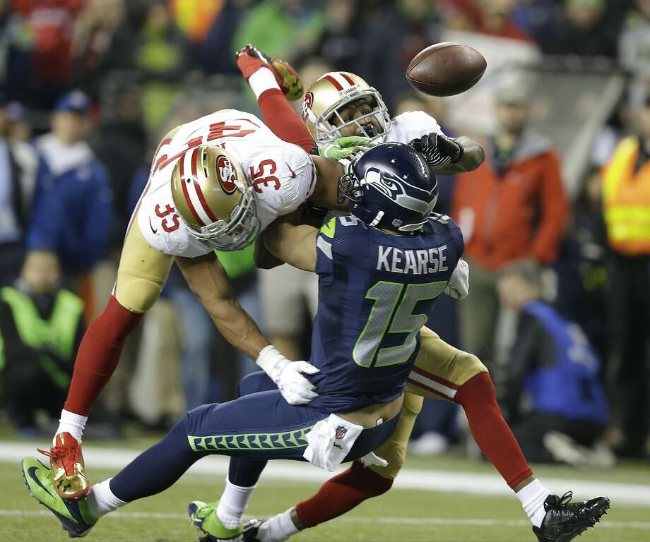 San Francisco 49ers' Eric Reid (35) and Donte Whitner (31) break up a pass intended for Seattle Seahawks' Jermaine Kearse during the second half of the NFL football NFC Championship game Sunday, Jan. 19, 2014, in Seattle. (AP Photo/Elaine Thompson) Photo: Elaine Thompson, Associated Press