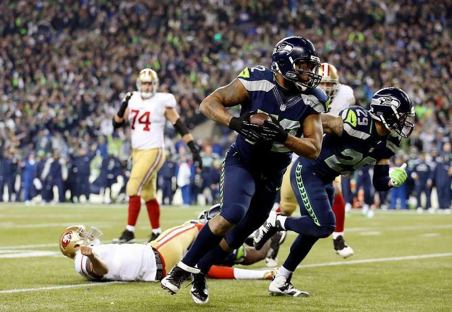 Seahawks defensive end Michael Bennett advances a fumble after 49ers quarterback Colin Kaepernick was leveled early in the fourth quarter in Seattle. Photo: Christian Petersen, Getty Images