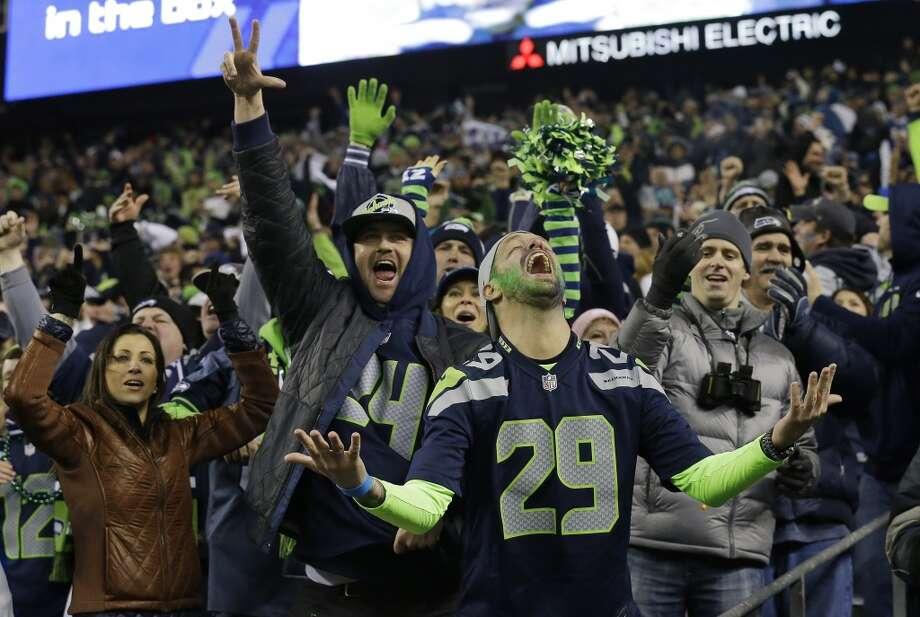 Seahawks fans react after a 40-yard touchdown run by Marshawn Lynch. Photo: Elaine Thompson, Associated Press