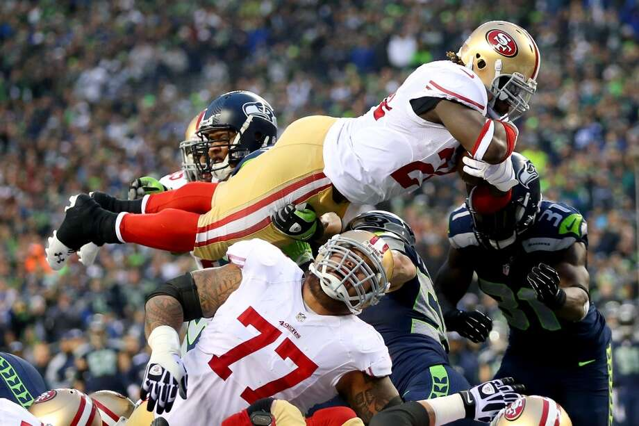 49ers running back Anthony Dixon dives over the pile for a touchdown against the Seahawks. Photo: Ronald Martinez, Getty Images