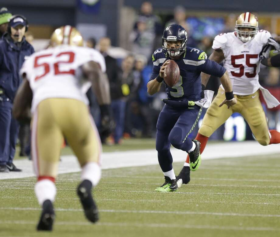 Seahawks quarterback Russell Wilson scrambles against the 49ers. Photo: Elaine Thompson, Associated Press