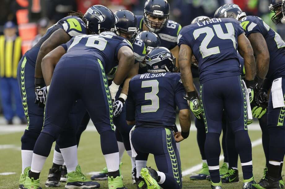 Seahawks quarterback Russell Wilson and the Seahawks huddle up during the NFC Championship game against the 49ers. Photo: Elaine Thompson, Associated Press