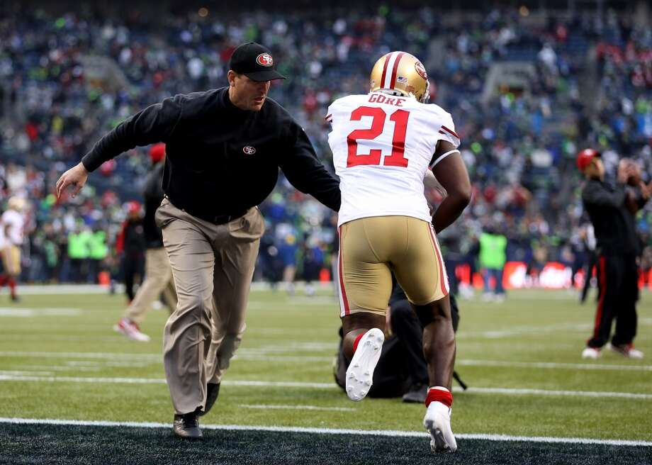 49ers coach Jim Harbaugh gives running back Frank Gore a handoff during warmups before the NFC Championship game against the Seahawks. Photo: Christian Petersen, Getty Images