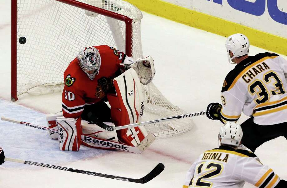 Chicago Blackhawks goalie Corey Crawford (50) blocks a shot by Boston Bruins' Zdeno Chara (33) during the overtime period of an NHL hockey game in Chicago, Sunday, Jan. 19, 2014. The Blackhawks won 3-2. (AP Photo/Nam Y. Huh) ORG XMIT: CXA113 Photo: Nam Y. Huh / AP