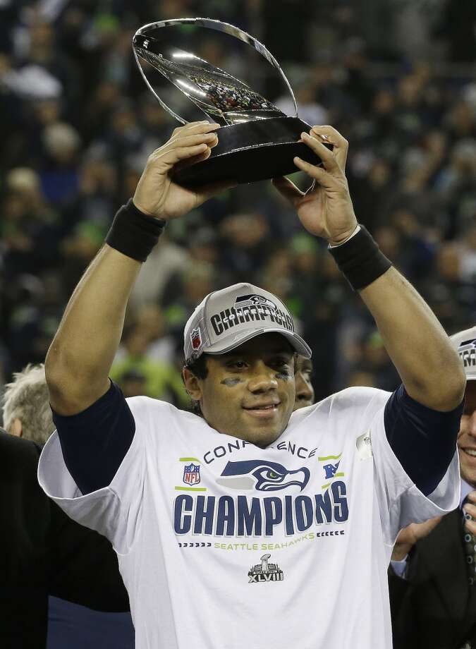 Russell Wilson holds up the George Halas Trophy after the game. Photo: Ted S. Warren, Associated Press