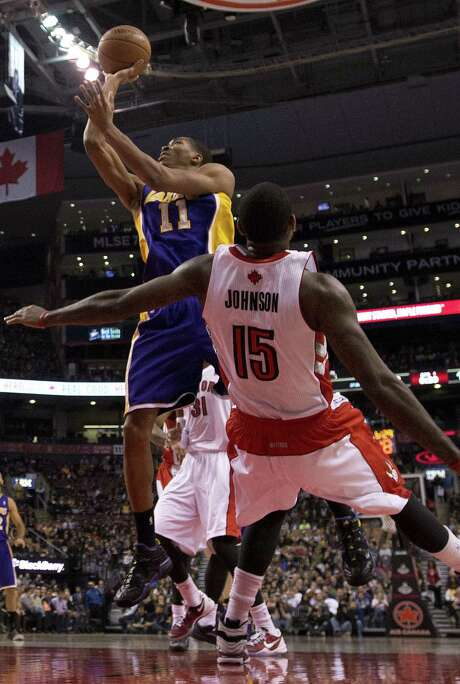 Lakers forward Wesley Johnson (left) picks up an offensive foul as he drives on the Raptors' Amir Johnson. Wesley Johnson finished with eight points. Photo: Frank Gunn / Associated Press / The Canadian Press