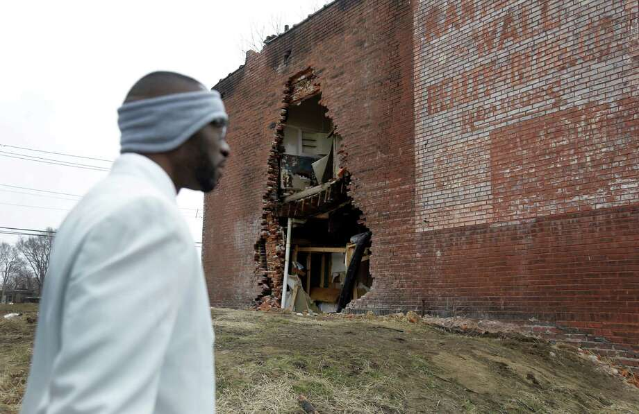In this Thursday, Jan. 16, 2014 photo, Melvin White, founder of the Beloved Streets of America project, walks past crumbling building during a tour of Dr. Martin Luther King Jr. Drive in St. Louis. The nonprofit is working to revitalize a downtrodden six-mile stretch of the drive named for the slain civil rights leader, marked by vacant lots, crumbling buildings and a preponderance of liquor stores, pawn shops and check-cashing businesses. Project leaders hope revitalize MLK's streets that have fallen into disrepair in cities around the country. (AP Photo/Jeff Roberson)  ORG XMIT: MOJR403 Photo: Jeff Roberson / AP